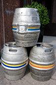 Three empty metal kegs outside a bar