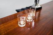 Three empty shot glasses on a bar