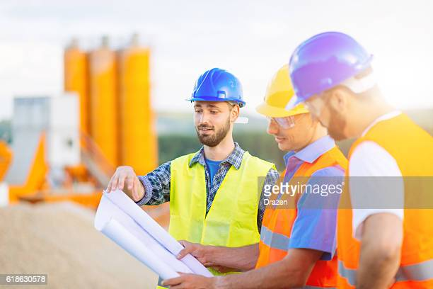 Three engineers on construction site with blueprint