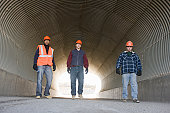 Three engineers walking in a tunnel at an asphalt plant