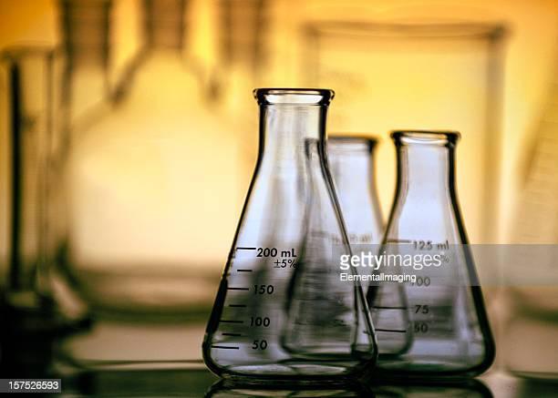 Three Erlenmeyer Flasks with Laboratory Glassware Background