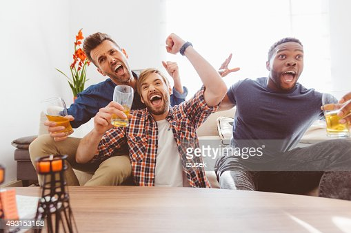 Three excited guys watching sport on tv