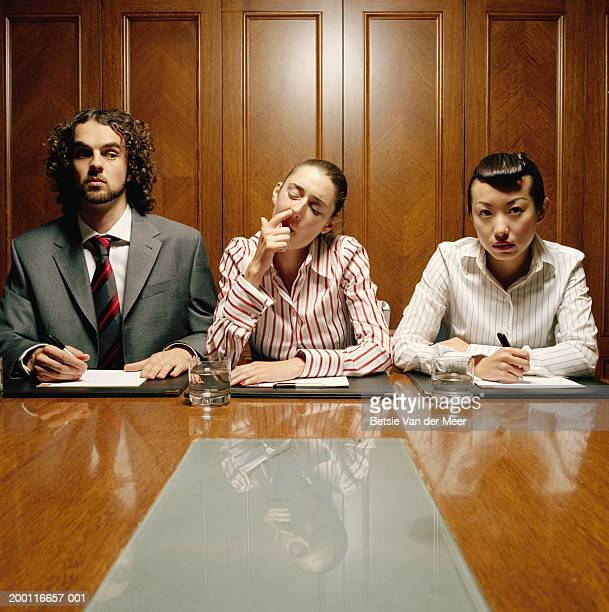 Three executives at desk, young woman in centre picking nose