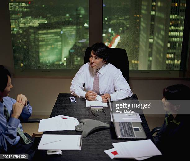 Three executives talking during business meeting, night, elevated view