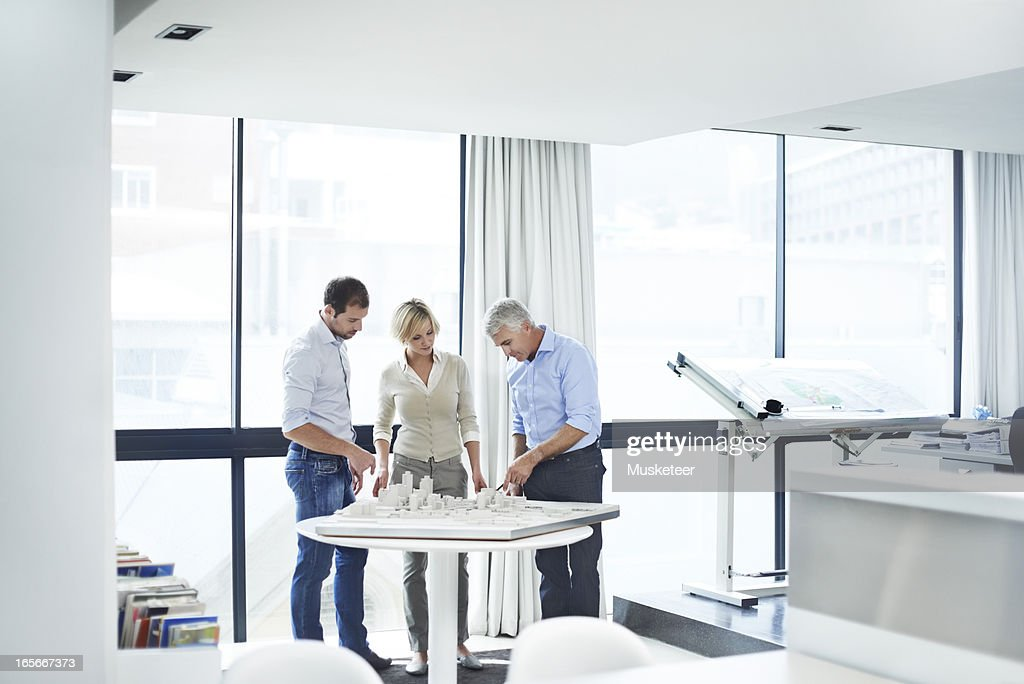 Three experienced architects in their studio : Stock Photo