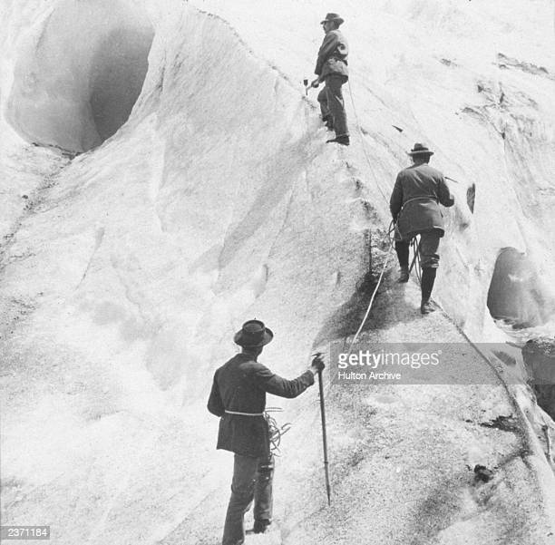 Three explorers cut steps into the ice of the Bossons Glacier as they ascend Mt Blanc in the French Alps France 1817