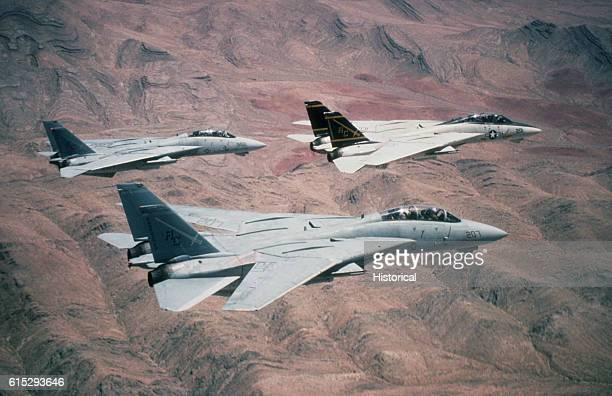 Three F14A Tomcat aircraft from Fighter Squadron 32 pass over the Saudi desert while on a training flight during Operation Desert Shield VF32 is...