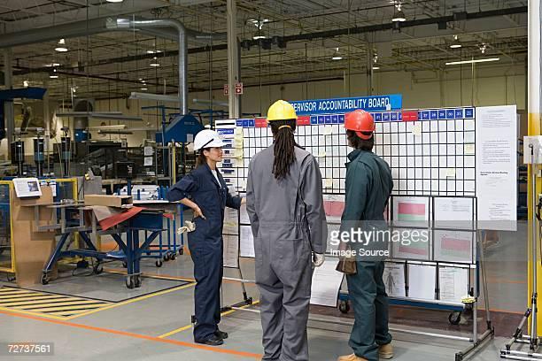 Trois ouvriers debout près de tableau de messages