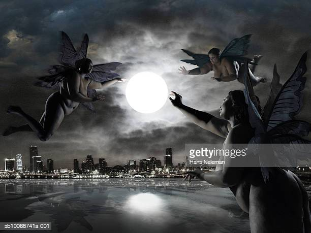 Three fairies reaching for glowing moon over cityscape (digital composite)