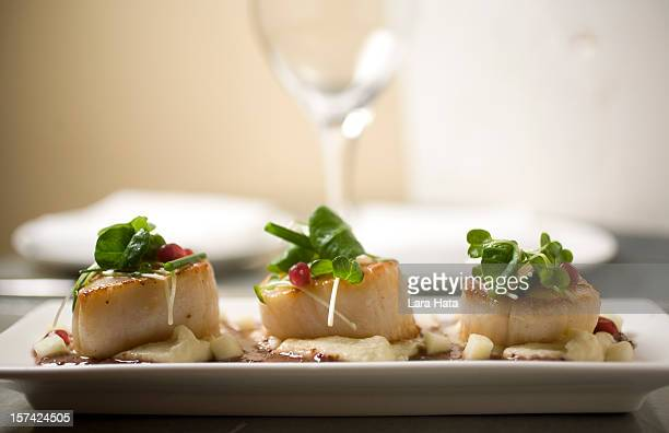 Three fancy scallops on a plate with parsley and sauce