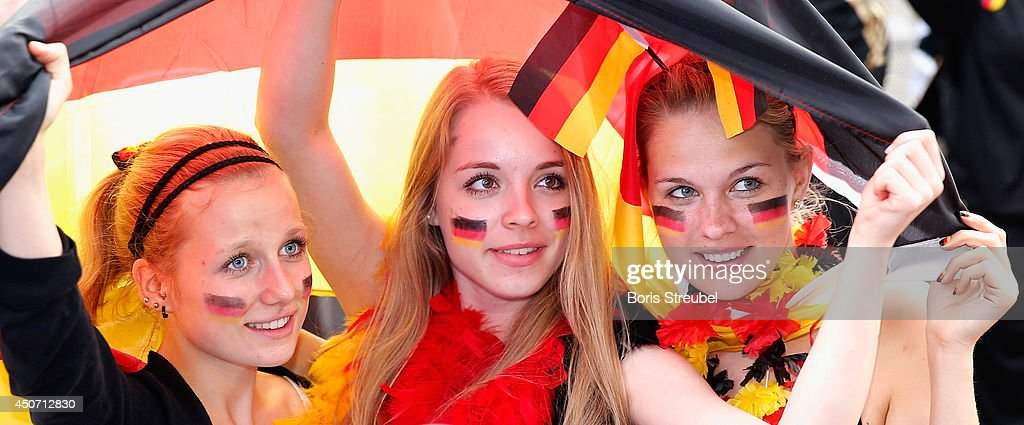 Three fans of Germany celebrate at the Fanmeile public viewing at Brandenburg Gate during the 2014 FIFA World Cup Brazil Group G match between Germany and Portugal on June 16, 2014 in Berlin, Germany.