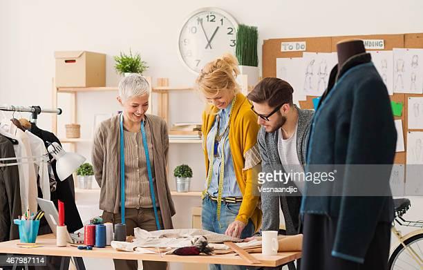 Three fashion designers around a table