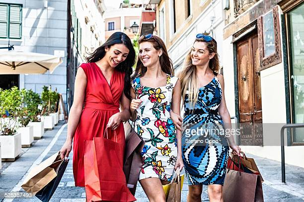 Three fashionable young women friends out shopping, Cagliari, Sardinia, Italy