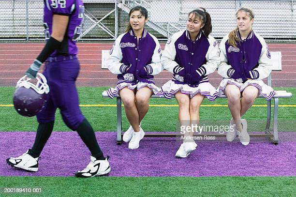 Three female cheerleaders (16-18) watching football player