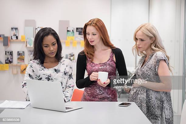 Three female colleagues looking at laptop, pregnant woman touching stomach