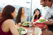 Three Female Friends Enjoying Lunch At Rooftop Restaurant Smiling And Laughing With Each Other.