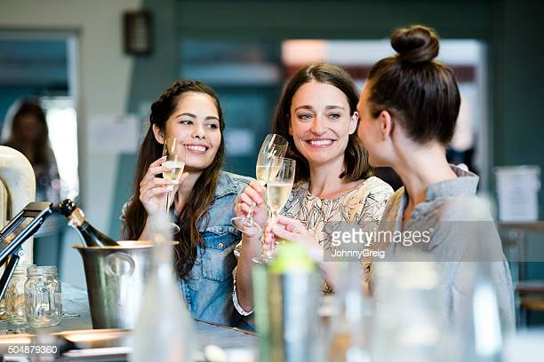Three female friends in bar enjoying glass of wine, talking