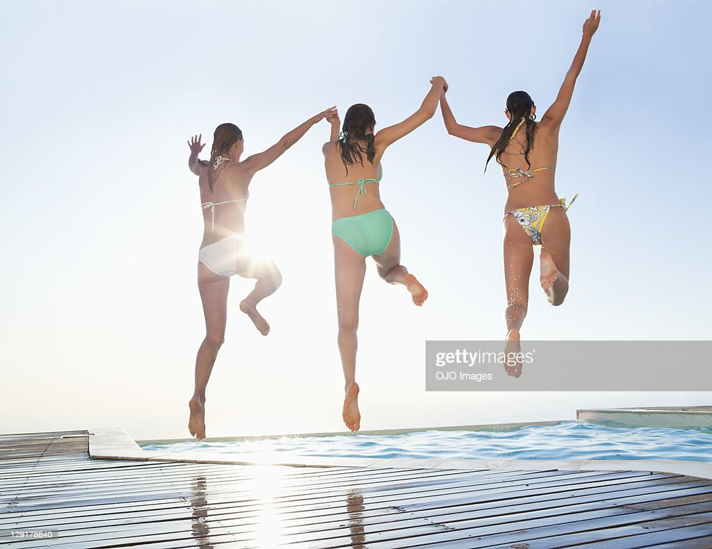Three female friends jumping in swimming pool : Stock Photo