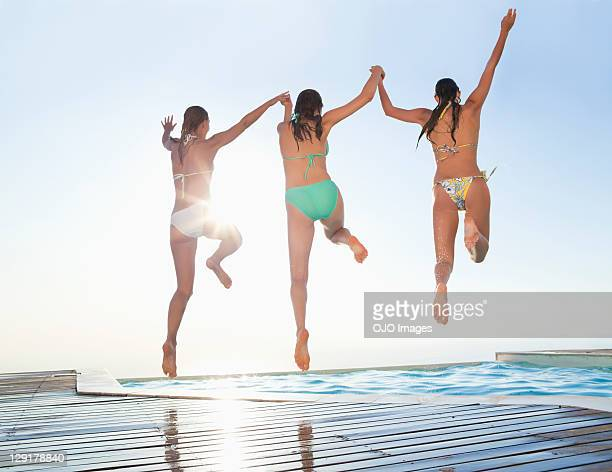 Three female friends jumping in swimming pool