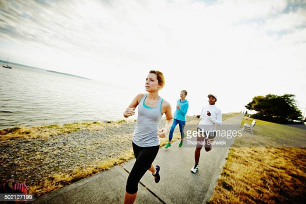 Three female friends running together on path