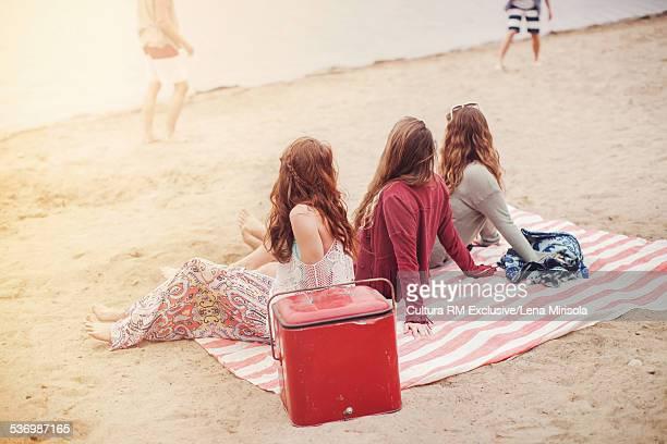 Three female friends sitting on picnic blanket on beach