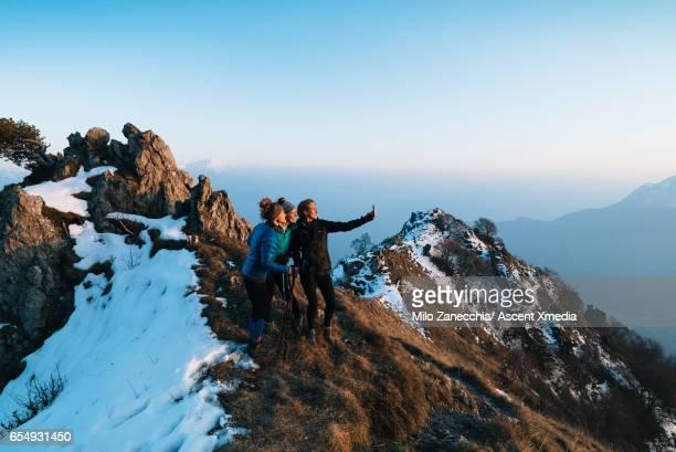 Three female hikers take selfie pic on mountain summit