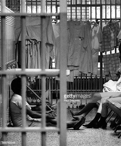 Three female inmates sit and chat inside their prison cell inside the Cook County Jail Chicago Illinois late 1960s or early 1970s Their dresses hang...