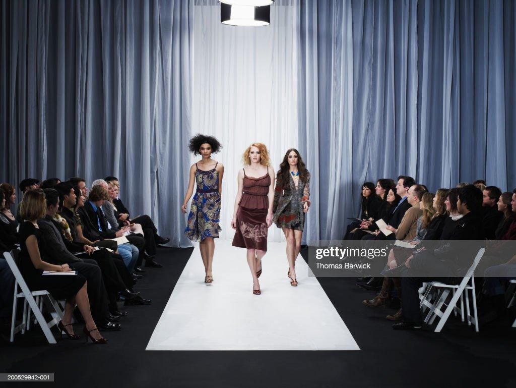 Three female models walking down runway : Stock Photo