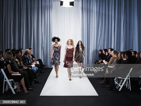 Three female models walking down runway