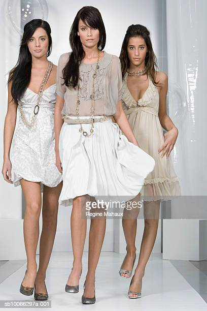 Three female models walking on catwalk