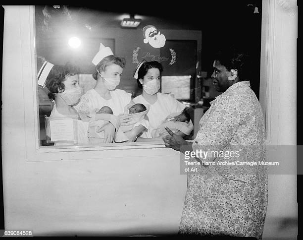 Three female nurses wearing light colored scrubs and hats holding babies in light colored blankets standing at hospital nursery window with Merry...