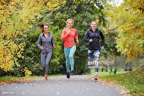 Three female runners running along park path