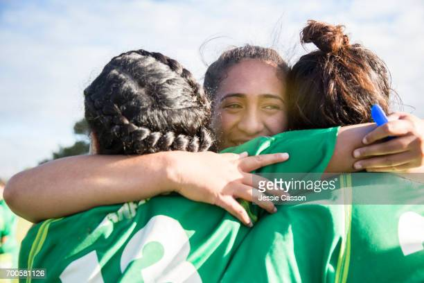 Three female sports players embrace