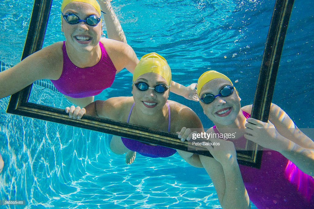 Three female swimmers, underwater, looking through frame