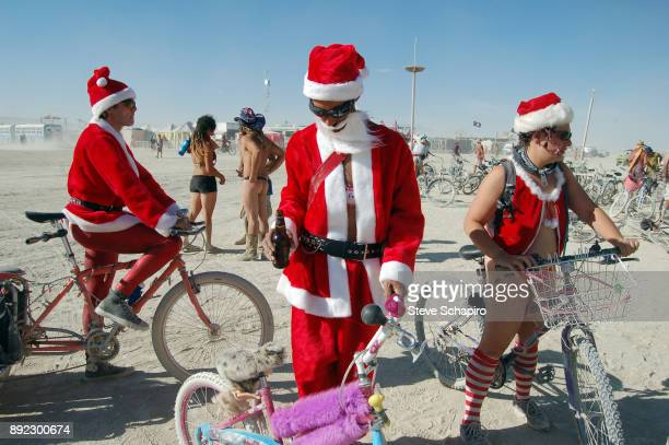 Three festival goers all dressed in Santa Claus costumes stand with bicycles during the Burning Man Festival in the Black Rock Desert Nevada...