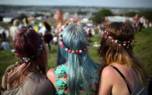 Three festival goers sit and look at the view at the Glastonbury Festival of Contemporary Performing Arts site at Worthy Farm Pilton on June 26 2013...