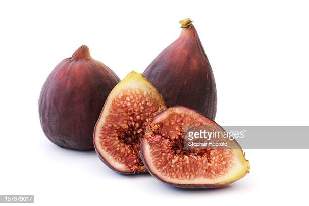 Three figs, one cut up for display, isolated on white