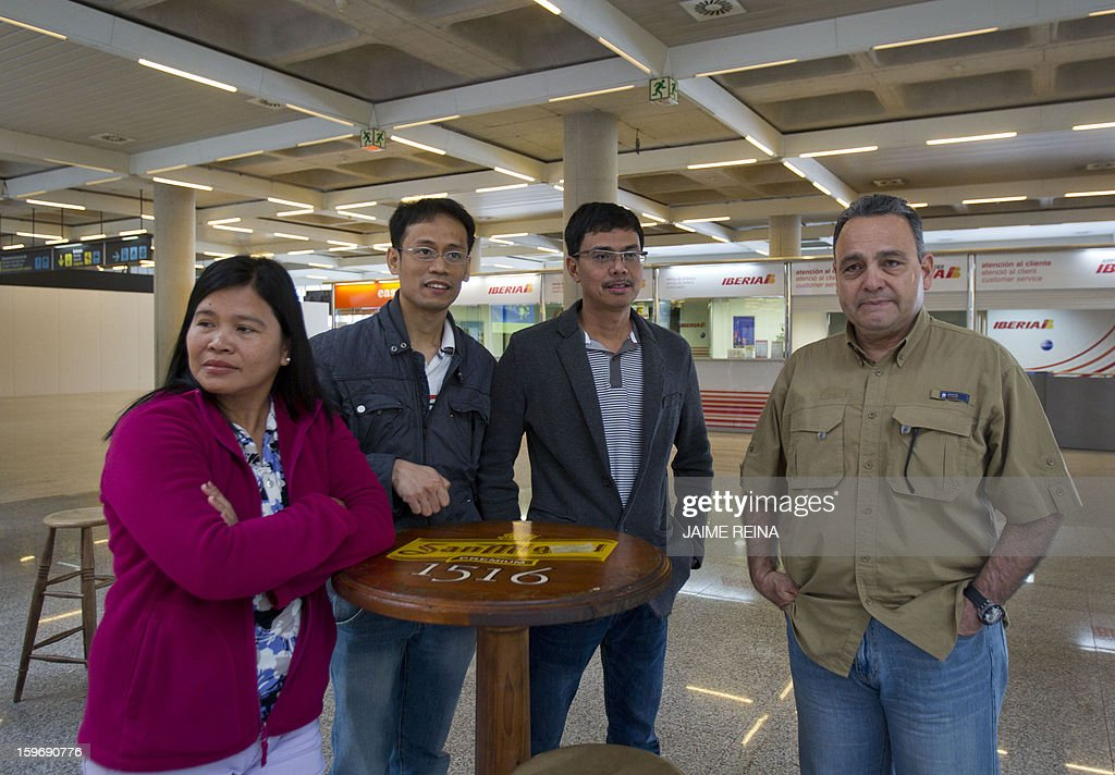Three Filipinos (L) and a Venezuelan employees of subcontracters working for British oil giant BP in Algeria wait for their flight to Uruguay at the Palma de Mallorca airport on January 18, 2013. Foreign workers leave Algeria following an Algerian army rescue operation launched at the In Amenas plant on January 17, 2013 after kidnappers seized hostages at the site in what they said was retaliation for Algeria's support for French air strikes in Mali. AFP PHOTO/ JAIME REINA