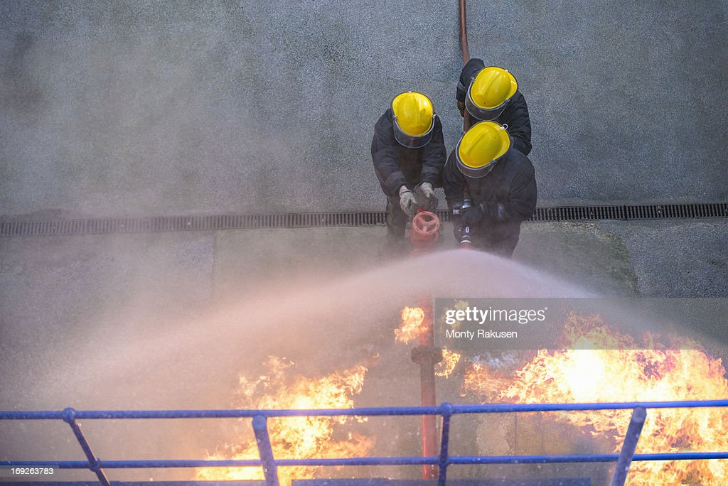 Three firefighters putting out fire in fire simulation training facility, overhead view : Stock Photo