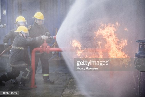 Three firefighters putting out fire in fire simulation training facility
