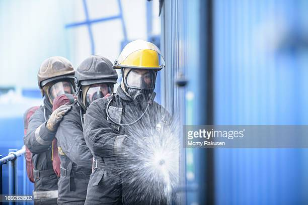 Three firefighters using hose in fire simulation training facility, front view