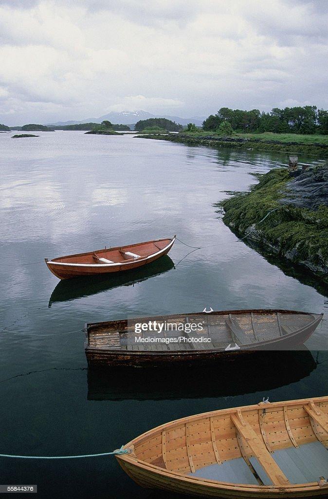 Three fishing boats moored at the beach, Hjertoya Island, Molde, Norway : Stock Photo
