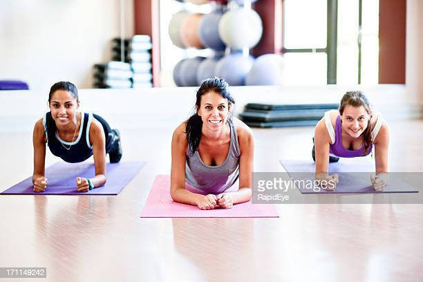 Three fit young women do Bridge exercise for core strength