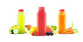 Three different flavors of cold freshly squeezed fruit and vegetable juice blended together in generic plastic bottles with red caps. The bottles are isolated on a white background with natural shadow