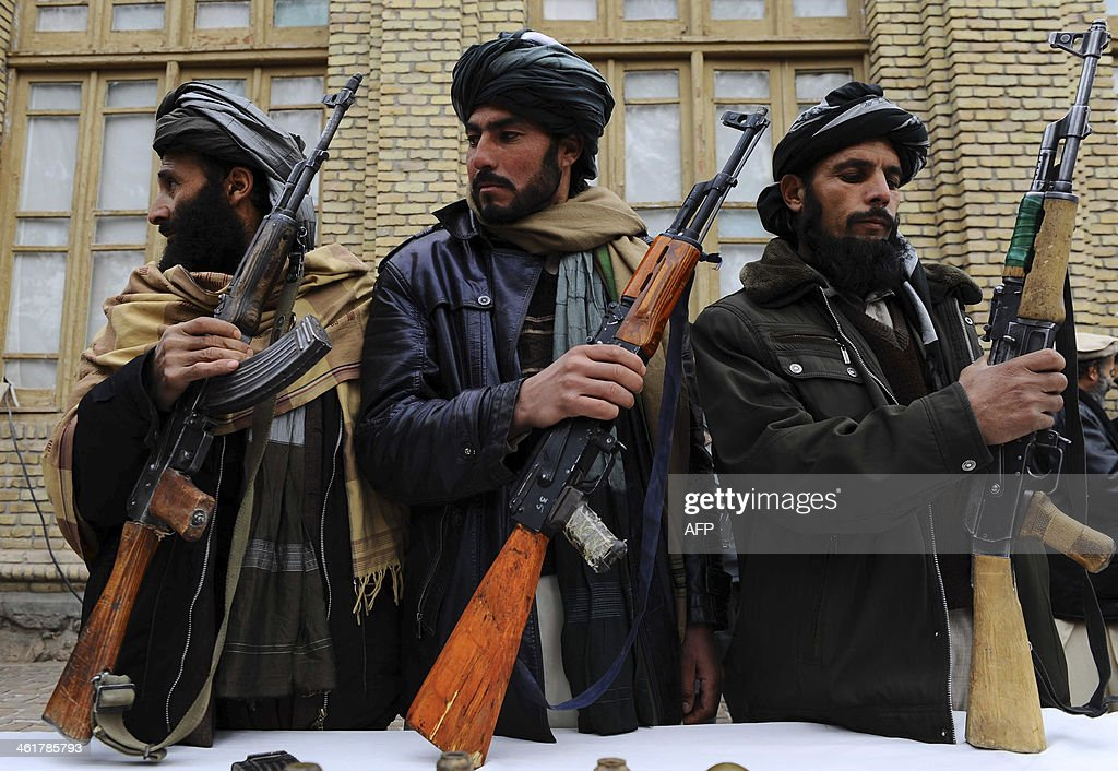 Three former Taliban fighters carry their weapons during a handover as they join a government peace and reconciliation process at a ceremony in Herat...