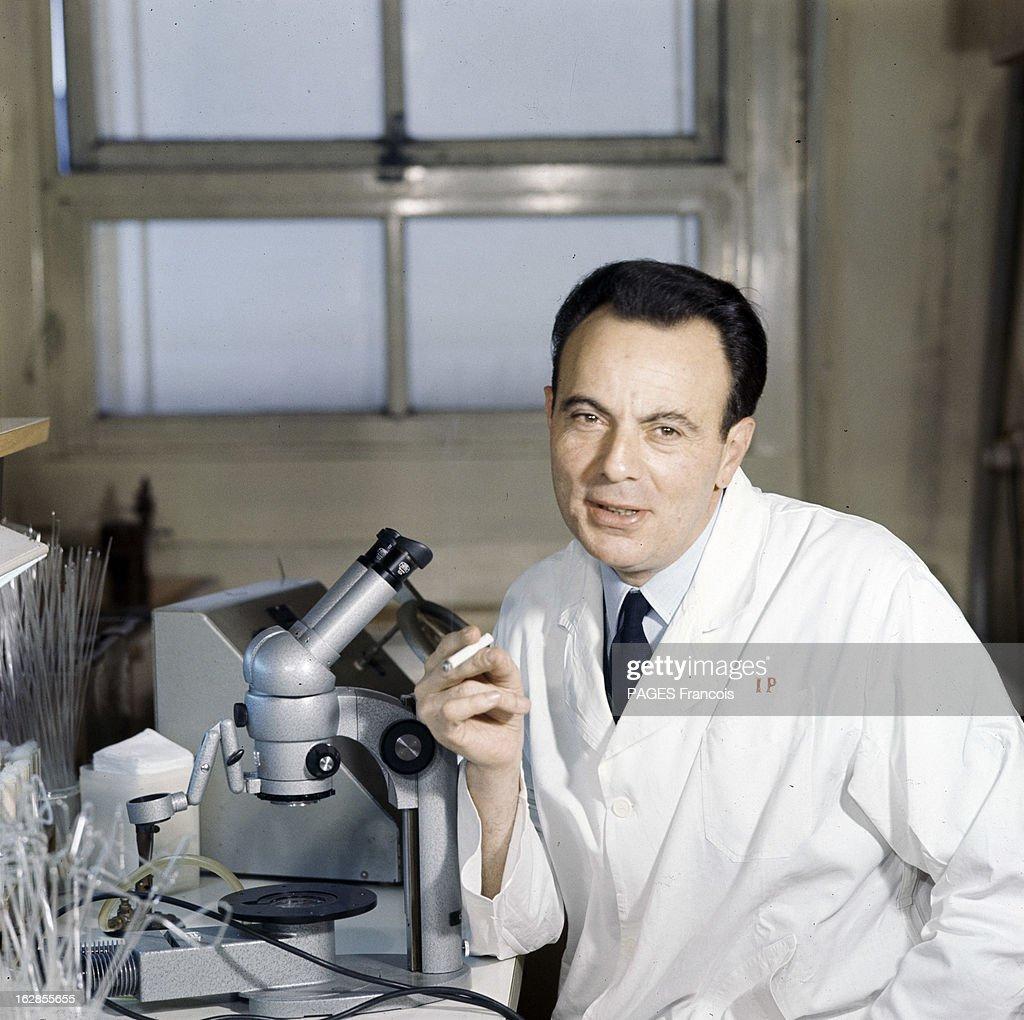 Three French Nobel Prize For Medicine. A Paris, l'Institut PASTEUR, François JACOB, en blouse blanche, avec une cravate, attablé devant un microscope, tenant une cigarette.