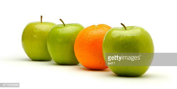 Three fresh green apples and one orange.