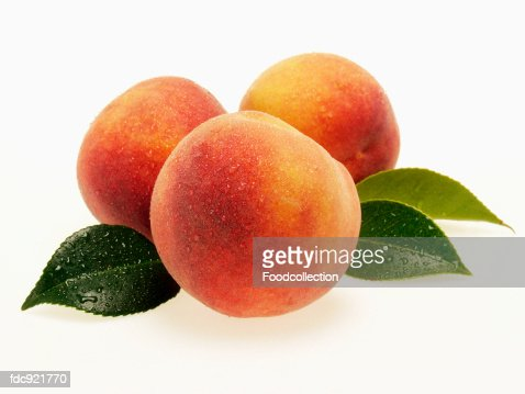Three fresh peaches with leaves and drops of water
