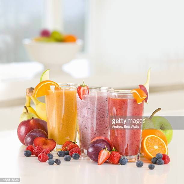 Three freshly made fruit smoothies and ingredients