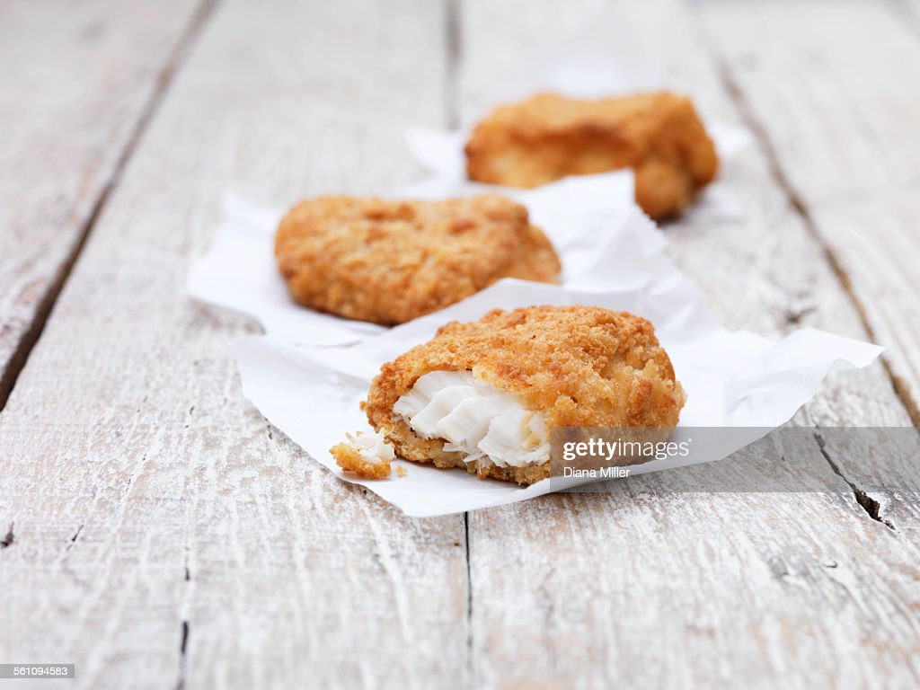 Three fried breaded chunky cod pieces on wooden table